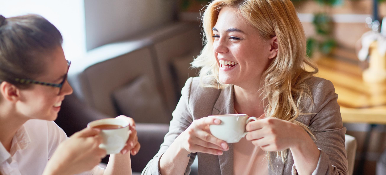 mulheres conversando sobre o trabalho e tomando café